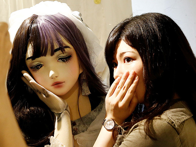 "A woman poses with ""doll"" model Lulu Hashimoto at an event with fans in Tokyo"